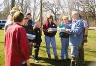 photo of many teaching a small group outdoors